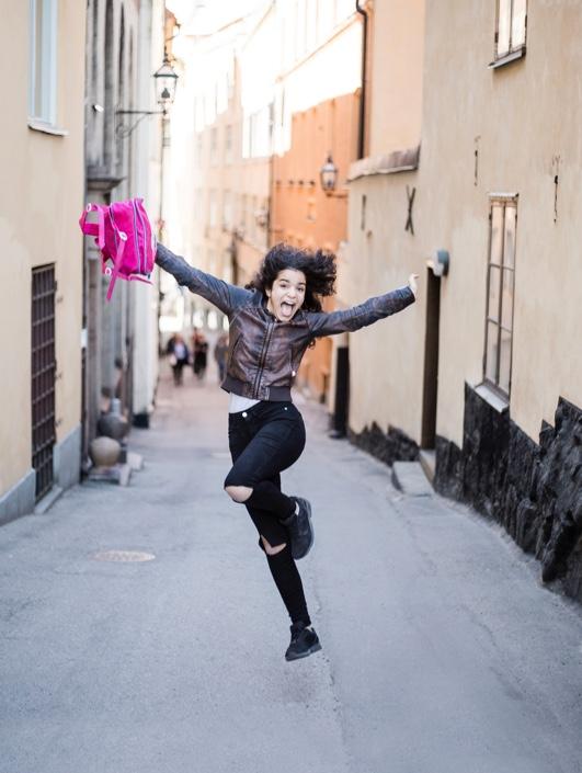 Bild på en glad tjej som tar ett skutt på en gata
